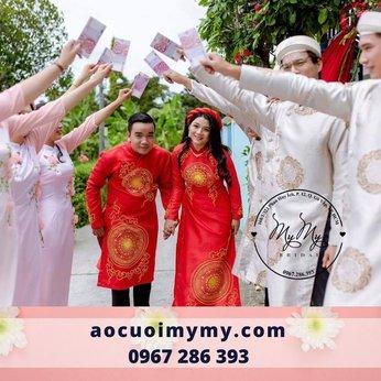 Áo dài cặp cô dâu chú rể chất liệu gấm đỏ vẽ hoa văn trống đồng, đính kết hạt chai